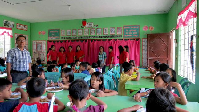 Reyn Cruz (standing, left) visits Anonas Elementary School in Urdaneta City to oversee the new food program supported by the Pangasinan Group of Manitoba. Cecile Cruz (fourth from right) stands with the school teachers.