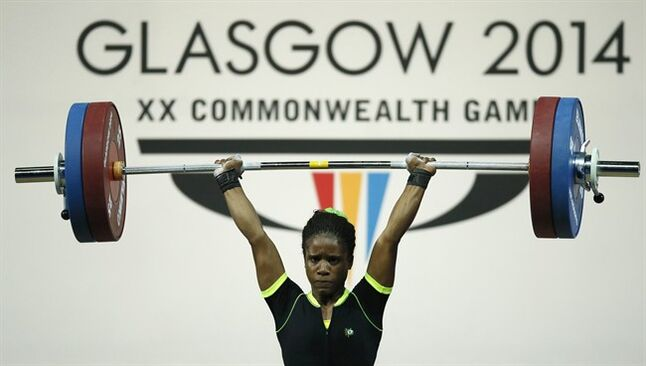 FILE - This is a Friday, July, 25, 2014 file photo of Chika Amalaha of Nigeria, as she makes good lift during the women's 53 kg weightlifting competition at the Commonwealth Games Glasgow 2014, in Glasgow, Scotland. The Commonwealth Games Federation says a 16-year-old Nigerian weightlifter has been stripped of her gold medal after a positive doping test it was reported on Friday, Aug. 1, 2014. Amalaha tested positive for diuretics and masking agents after winning the 53-kilogram (117-pound) division last Friday, becoming the youngest ever female to win a weightlifting title at a Commonwealth Games. (AP Photo/Alastair Grant, File)