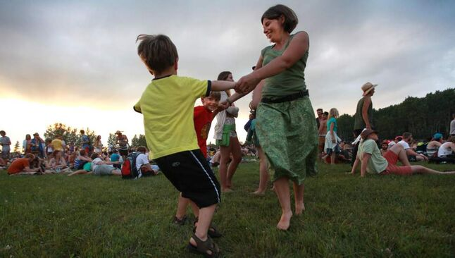 Heidi Fauet dances with her son Sam (red shirt) and his friend Silas Solum near the Main Stage during the opening night at the 39th annual Winnipeg Folk Festival at Birds Hill Park Wednesday night.   Ruth Bonneville / Winnipeg Free Press