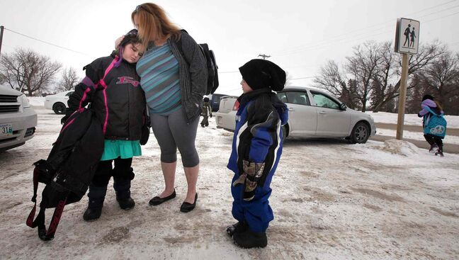 Sandra Ducharme comforts her daughter, Haylee, as little brother Connor looks on outside St. Andrews School. Haylee was a schoolmate of the late Gracie Herntier-Clark. 'I'm sad because of my friend,' she said.