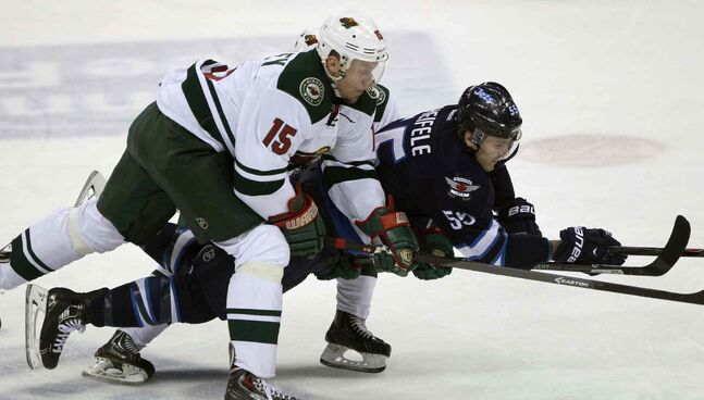 Winnipeg Jets forward Mark Scheifele (centre) gets hauled down by  Minnesota Wild skaters Dany Heatley (left) and Mikael Granlund during the first period.