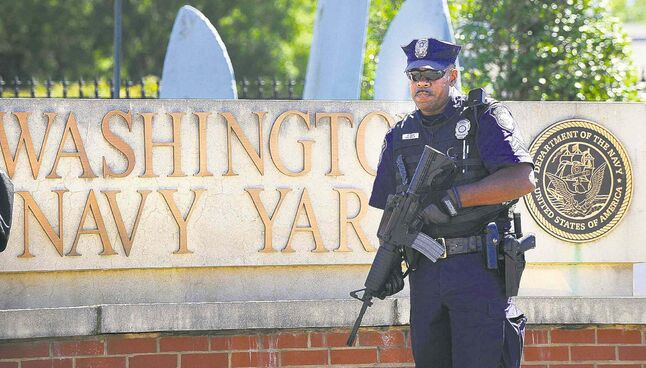 An armed officer, who said he was from the Department of Defence, stands guard at the front gate of the Washington Navy Yard Tuesday.