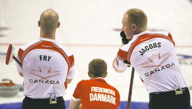 Jonathan Hayward / THE CANADIAN PRESSCanadian skip Brad Jacobs talks with his third, Ryan Fry, while Danish third Johnny Frederiksen lines up a shot during the afternoon draw at the world men�s curling championship in Victoria, B.C., Thursday.