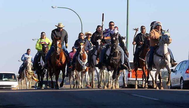 Canupawakpa riders head down Brandon's busy 18th Street on their way to the courthouse Tuesday.