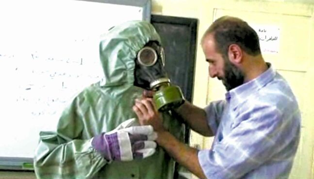 This image made from video shows a volunteer adjusting a student's gas mask in Aleppo, Syria.