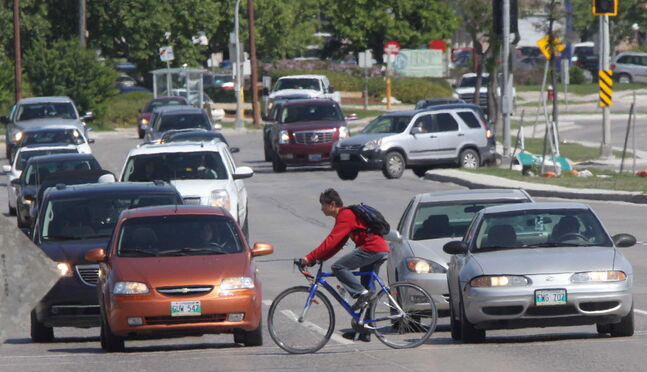 A cyclist rides at Bishop Grandin Boulevard and Pembina Highway Thursday afternoon.