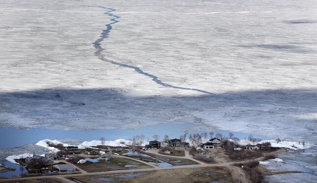 An aerial shot shows the community of Ochre Beach, with open water between the ice floe along the shore and the ice that stretches out to Dauphin Lake.