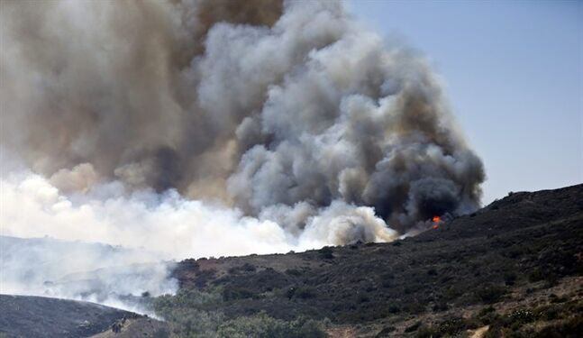 Billowing smoke rises from flames as firefighters begin the trek up the hills to battle a wild fire, Tuesday, May 13, 2014, in San Diego. Wildfires destroyed a home and forced the evacuation of several others Tuesday in California as a high-pressure system brought unseasonable heat and gusty winds to a parched state that should be in the middle of its rainy season. (AP Photo)