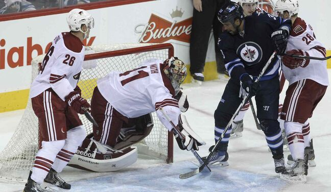 Winnipeg Jets' Dustin Byfuglien (33) takes care of Phoenix Coyotes' goaltender Mike Smith (41) just as Winnipeg Jets' Blake Wheeler (26) (out of frame) puts the puck into the net during the first period of Thursday's game.