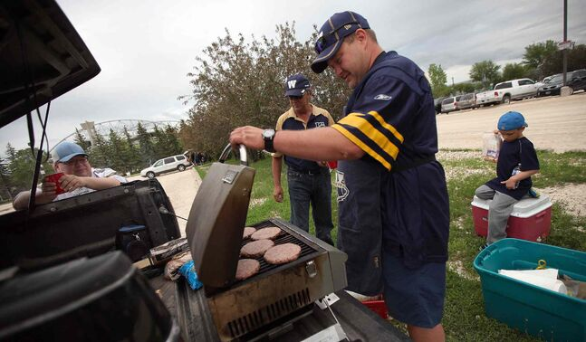 Tailgaters kick back with some burgers before the Winnipeg Blue Bombers home opener football game Thursday. From left, Cory Rach, Pat Mulville, Kurt Kowalchuk and six-year-old Brady Rach get the grill going.