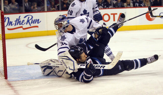 Winnipeg Jets' Chris Thorburn crashes Toronto Maple Leafs Goalie James Reimer during the 3rd period Thursday night at MTS Centre.