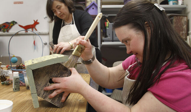 Karen Lehr paints a birdhouse for DASCH's gift store on St. Anne's Road during the official opening Wednesday.