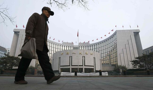 An elderly Chinese man walks past the headquarters of the People's Bank of China (PBOC) in Beijing, China, Tuesday, March 11, 2014.
