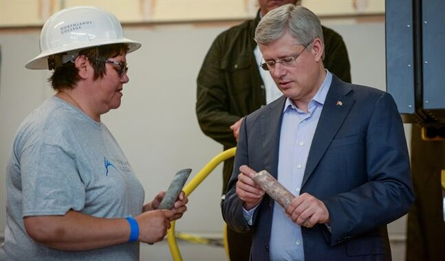 Prime Minister Stephen Harper looks at a core segment of granite as he talks with a member of the Northlands College staff during a media event at Northlands College in Air Ronge, Sask., Wednesday, July 30, 2014. THE CANADIAN PRESS/Matt Smith