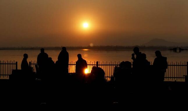 Kashmiri residents and tourists watch the last sunset of the year 2012, at the Dal Lake in Srinagar, India.