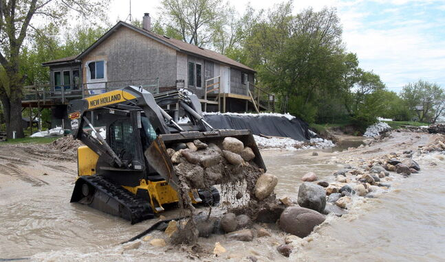 Heavy equipment works to save a cottage at Twin Lakes Beach in 2011.
