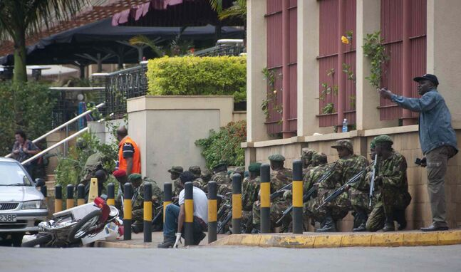 Armed police crouch down and take position during a gun battle outside the Westgate Mall in Nairobi, Kenya, Saturday. Gunmen threw grenades and opened fire Saturday killing at least 22 people in an attack targeting non-Muslims at an upscale mall in Kenya's capital that was hosting a children's day event, a Red Cross official and witnesses said.
