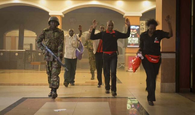 Civilians who had been hiding during the gun battle hold their hands in the air as a precautionary measure before being searched by armed police leading them to safety, inside the Westgate Mall in Nairobi, Kenya, Saturday. Gunmen threw grenades and opened fire Saturday, killing at least 22 people in an attack targeting non-Muslims at an upscale mall in Kenya's capital that was hosting a children's day event, a Red Cross official and witnesses said.