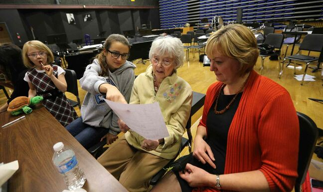 Kay Tworek (middle) and her daughter, Glenlawn Collegiate community liaison worker Margaret Lapenskie, look at part of the script with cast members Carina McLennan (second left) and Anni Irving (left) during rehearsal on Mon., Nov. 4, 2013, for the Glenlawn Collegiate's Remembrance Day production of Pig Dog,  which is based on Tworek's experiences during the Second World War.