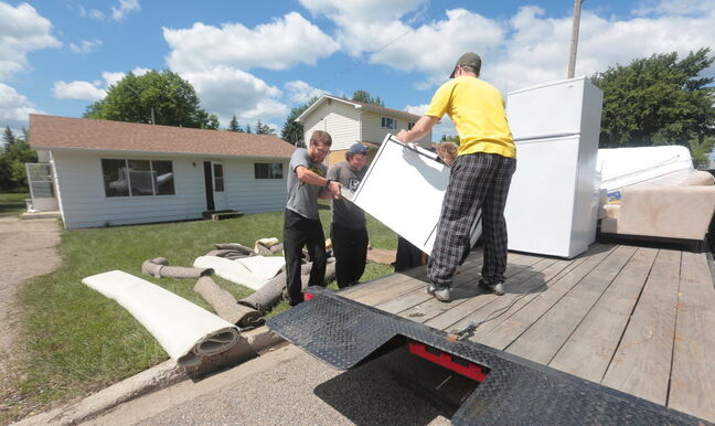 Brothers Joel, Kyle and Nick Martens help friend Jared Davies (right) move appliances from a friend's home in Virden Wednesday.