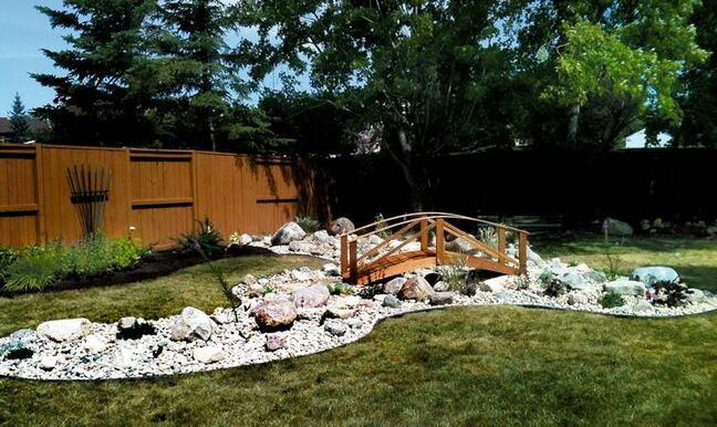 This Creek Bed look uses lawn edging, Riverbed Stone, small- to medium-sized boulders and a foot bridge. Planted among the rocks are perennials of different heights.