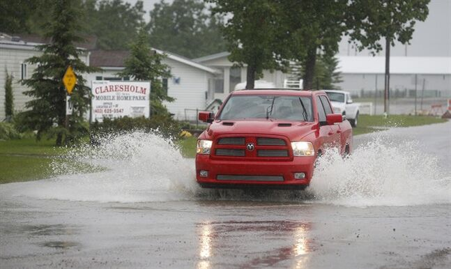 A truck sprays water as its driven through flood waters in Claresholm, Alta., Wednesday, June 18, 2014. THE CANADIAN PRESS/Jeff McIntosh