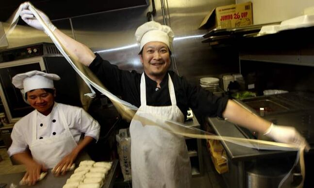 Jun Yang 'rips' a strip of freshly made noodles