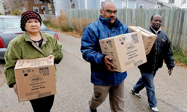 Asha Kinnarath (left), Hussain Guisti and Sam Taylor help assemble Attawapiskat package.
