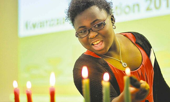 Tolu Oladele lights the last candle during the Kwanzaa celebration Sunday at the Caribbean Community Cultural Centre.