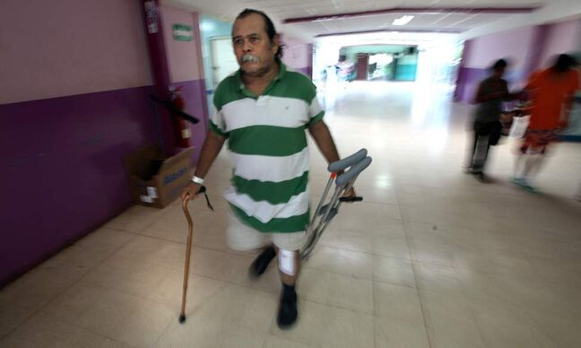 Using a single cane and carrying his crutches Juan Canda leaves the hospital in Managua for home four days after