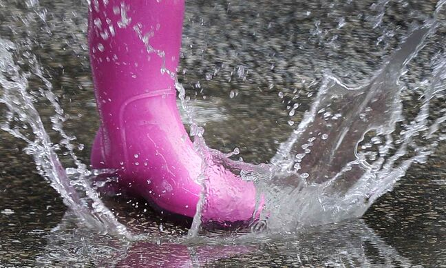 Suzy Willig runs through puddles at The Ex Sunday.