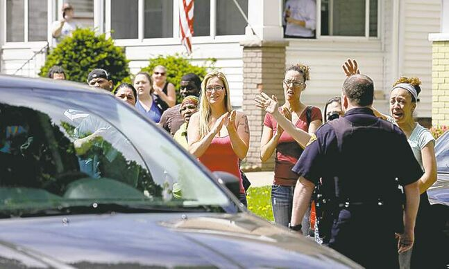 Neighbours and friends of Amanda Berry clap as she arrives at her sister's home in Cleveland  Wednesday.  Frustrated  neighbours lay blame on the authorities -- and each other -- for the ordeal that    saw Berry  separated from family and friends for a decade.