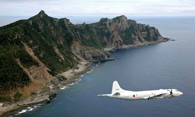 In this file photo, Japan Maritime Self-Defense Force's P-3C Orion surveillance plane flies over the disputed islands in the East China Sea, called the Senkaku in Japan and Diaoyu in China.
