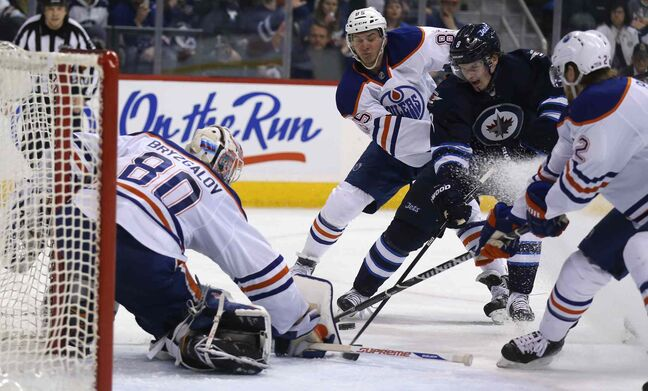 Edmonton Oilers' goaltender Ilya Bryzgalov (80) stops Winnipeg Jets' Anthony Peluso (14) as he drives between Oilers' Martin Marincin (85) and Jeff Petry (2) during the second period Saturday.