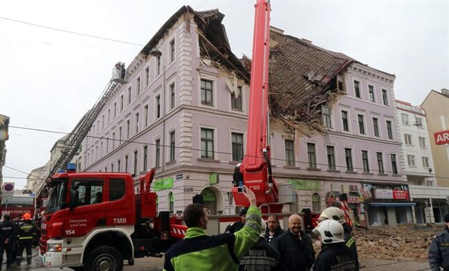 Firefighters and police are busy at a building damaged by an explosion in Vienna, Austria, Saturday, April 26, 2014. Austrian police say at least six people have been injured after the building collapsed following the reported explosion. (AP Photo/Ronald Zak)