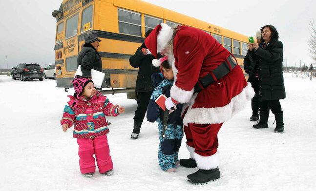 Late arrivals manage to sneak in some hugs as Santa heads out to the helicopter after visiting the Black River Anishinabe School on the Little Black River First Nation.