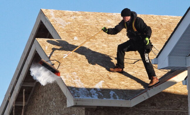 A construction worker cleans off the roof of a house being built in the Bridgewater Lakes development.