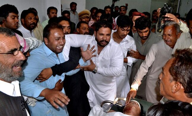 Pakistani men mourn over the lifeless body, bottom right, of a provincial lawmaker Handery Masieh at a local hospital in Quetta, Pakistan, Saturday, June 14, 2014. A guard for a provincial Christian lawmaker shot and killed the legislator during a meeting Saturday in southwest Pakistan, police said. Government spokesman Jan Mohammad Buledi said the guard fled after the attack and police were trying to arrest him.
