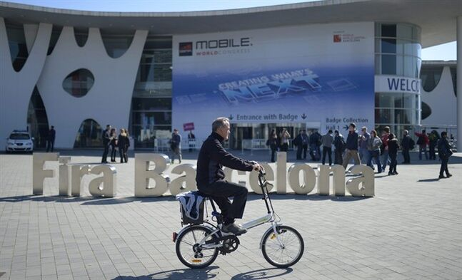 A man rides his bicycle outside the Mobile World Congress, the world's largest mobile phone trade show in Barcelona, Spain, Sunday, Feb. 23, 2014. (AP Photo/Manu Fernandez)