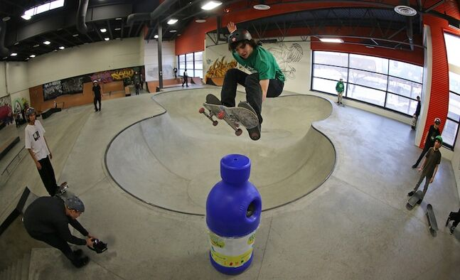 A young skateboarder jumps out of the pool and above a recycling bin at The Edge Skatepark, part of the Youth for Christ Centre for Youth Excellence.