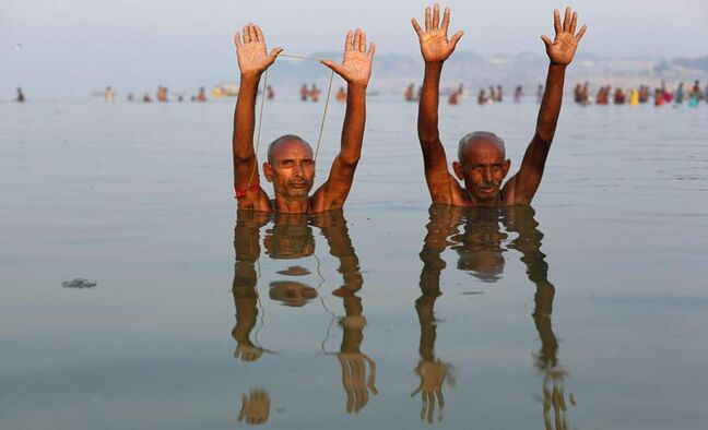 Hindu devotees offer prayers while taking a holy dip in the Ganges River on the first day of Navratri festival, in Allahabad, India, Tuesday, Oct. 16, 2012. Feasting and fasting takes over normal life for millions of Hindus during Navratri, the festival of nine nights. (AP Photo/Rajesh Kumar Singh)