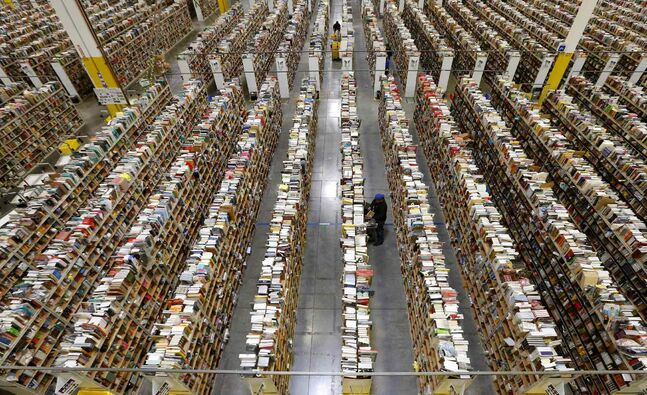An Amazon.com employee stocks products along one of the many miles of aisles at an Amazon.com Fulfillment Center in Phoenix.