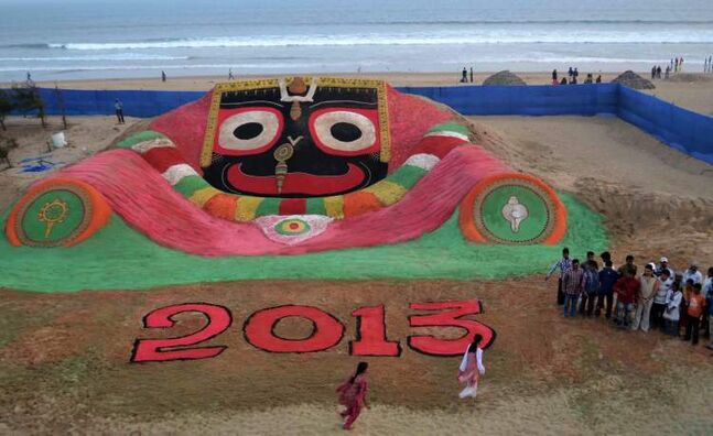 Indian people look at the sand sculpture for the new year 2013 created by sand artist Sudarshan Pattnaik at the Puri sea beach, 67 kilometres away from the eastern Indian city Bhubaneswar, India, Monday, Dec. 31, 2012.