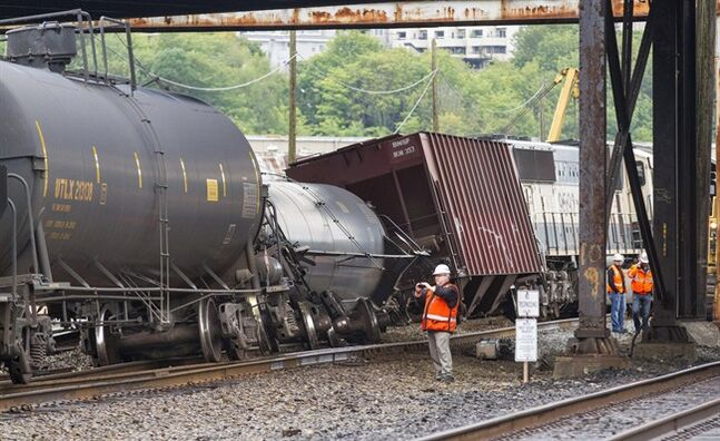 CORRECTS DATE TO JULY 24, NOT JULY 14 - An investigator photographs the scene where a locomotive and cars carrying crude oil went off the track beneath the Magnolia Bridge in the Interbay neighborhood of Seattle, Thursday morning, July 24, 2014. (AP Photo / The Seattle Times, Mike Siegel) SEATTLE OUT; USA TODAY OUT; MAGS OUT; TELEVISION OUT; NO SALES; MANDATORY CREDIT TO BOTH THE SEATTLE TIMES AND THE PHOTOGRAPHER