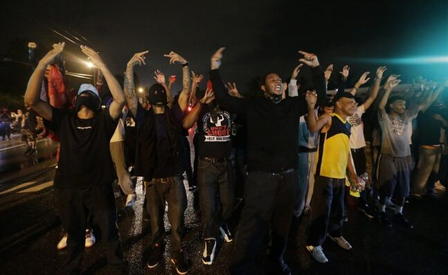 People defy a curfew Sunday, Aug. 17, 2014, before smoke and tear gas was fired to disperse a crowd protesting the shooting of teenager Michael Brown last Saturday in Ferguson, Mo. Brown's shooting in the middle of a street following a suspected robbery of a box of cigars from a nearby market has sparked a week of protests, riots and looting in the St. Louis suburb. (AP Photo/Charlie Riedel)