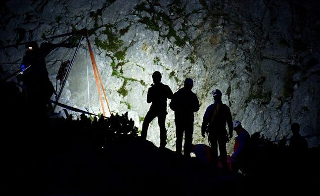 Members of the mountain rescue service stand next to the entrance of the Riesending cave near Marktschellenberg, southern Germany, early Thursday June 19., 2014. Germany's mountain rescue service said after a short pause overnight, its team resumed work early Thursday morning to bring Johann Westhauser the final 180 meters (590 feet) to the surface. The going has been slow as rescuers have had to haul Westhauser by hand through the narrow winding passage. Westhauser was injured June 8 while nearly 1,000 meters (3,280 feet) underground in the Riesending cave system in the Alps near the Austrian border. (AP Photo/dpa,Nicolas Armer)
