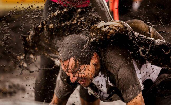 Guy Dugas crawls through the mud pit near the finish line of the Dirty Donkey Mud Run Saturday morning.