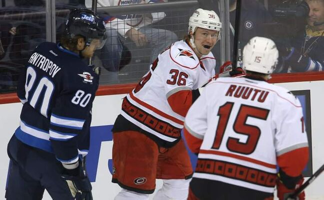 Winnipeg Jets' Nik Antropov looks on as Carolina Hurricanes' Jussi Jokinen (36) and Tuomo Ruutu celebrate a goal by Jokinen during the first period.