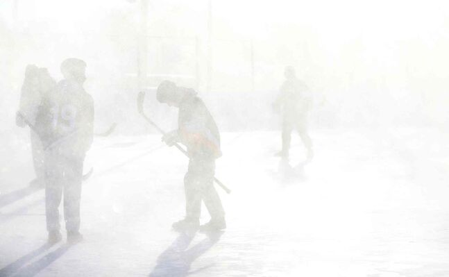 Members of the Tumbleweeds and the Mighty Puckin' Drunks are completely covered in snow from a passing snow blower during their spongee game at Melrose Park Community Centre.