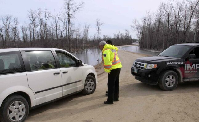 Security guards prevent a vehicle from entering Jenny Drive at  Whitetail Trail in the Petersfield area Wednesday morning. High water levels from nearby creeks flowing into Netley Lake caused the evacuation of homes earlier.